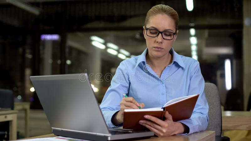 Patron de Madame corrigeant le programme dans le carnet, les réunions de planification et les conférences image stock
