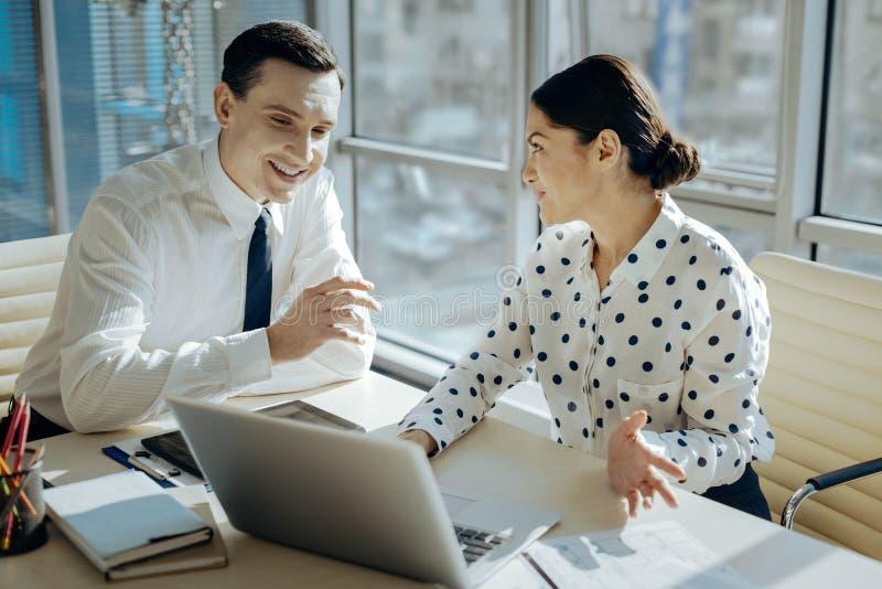 Patron féminin avec du charme commentant le rapport des employés photos stock
