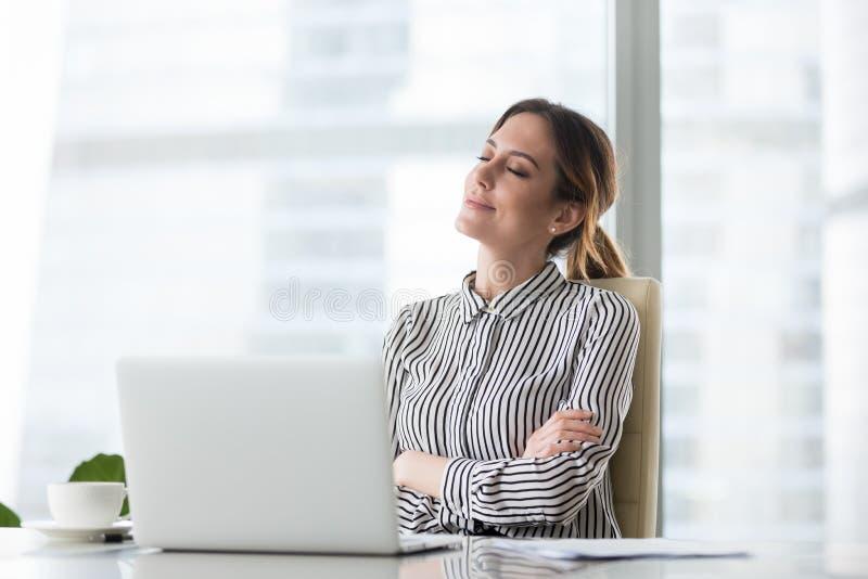 Patron féminin de sourire détendant dans la chaise de bureau avec des yeux fermés photographie stock libre de droits