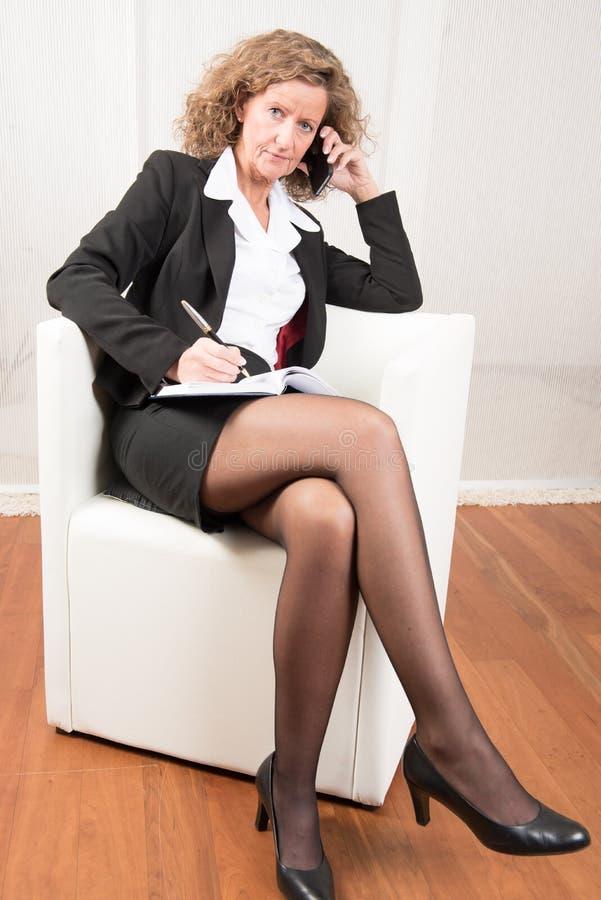 Patron féminin parlant à quelqu'un au téléphone image libre de droits