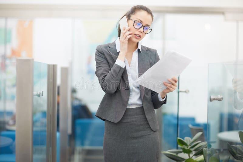 Patron femelle en parlant par le téléphone photo stock