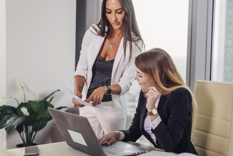 Patron femelle montrant des documents à l'assistant personnel donnant des instructions et des tâches image libre de droits