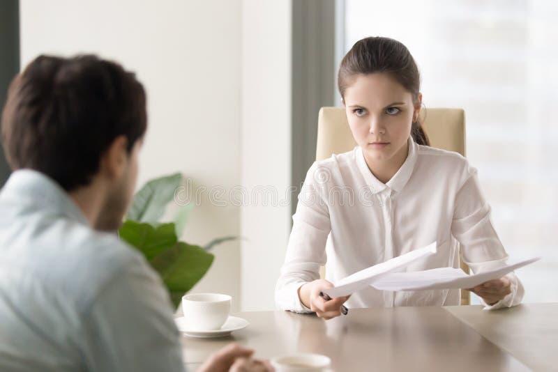 Patron femelle regardant fâché mécontent avec le travail masculin r des employés photographie stock libre de droits