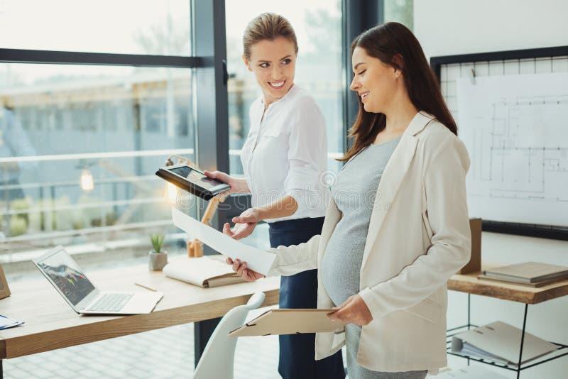 Patron gai souriant tout en prenant les documents d'un employé enceinte photo stock