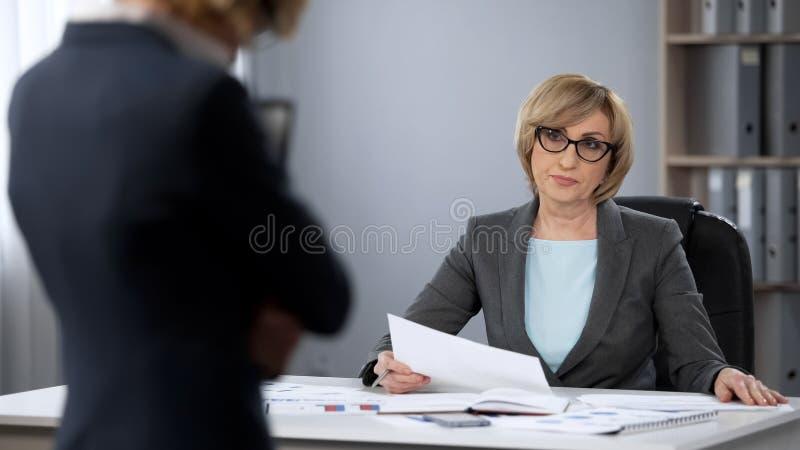 Patron sérieux strict de dame regardant avec mépris le secrétaire, dégradation des performances images stock