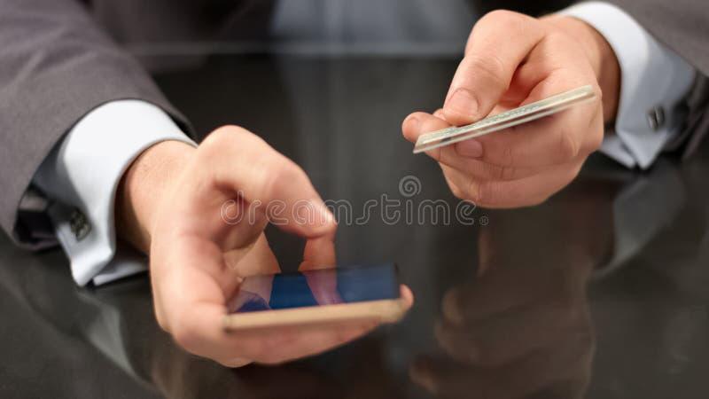 Patron utilisant des opérations bancaires mobiles sur le smartphone, insérant le numéro de carte, paiement en ligne photo stock