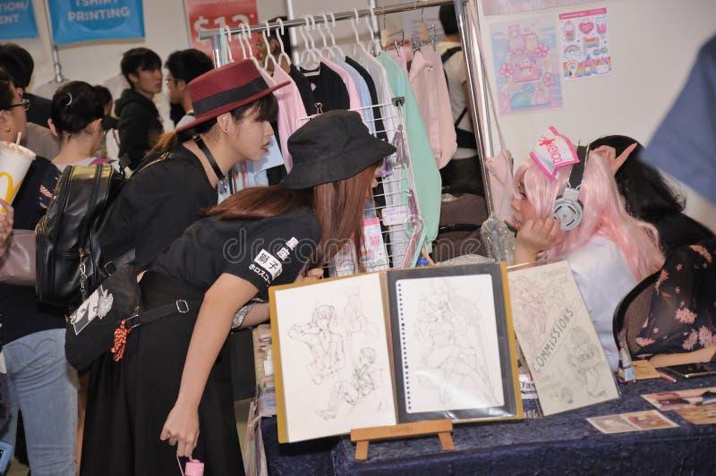 Patrons s'enquérant au sujet des marchandises chez Cosfest à Singapour photographie stock