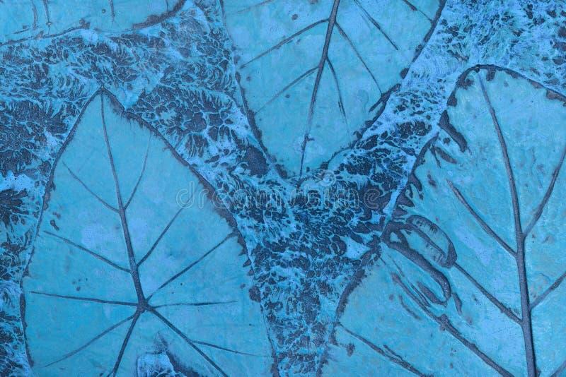 Patroon van blad op blauwe pastelkleur concrete bestrating wordt het gestempeld voor verfraait gangen in de tuin die stock afbeelding