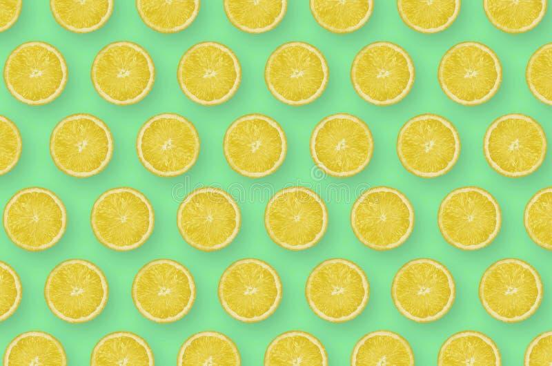 Patroon van de gele plakken van de citroencitrusvrucht op heldergroene achtergrond royalty-vrije stock foto