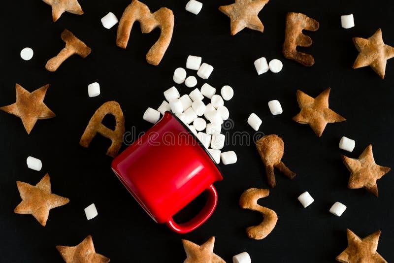 patroon van gemberkoekjes in de vorm van sterren en letters met vrolijke kerst en rode mok met ondiepe puinhoop op een stock fotografie