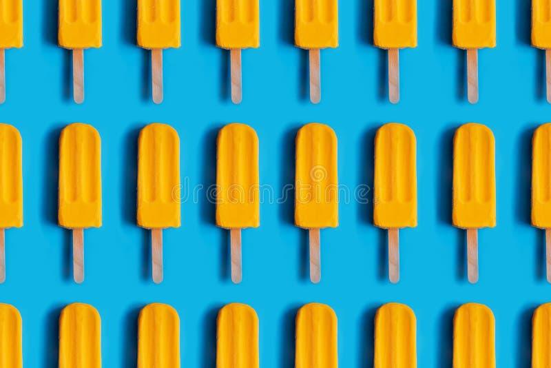 Patroon van helder geel mangoroomijs wordt gemaakt op blauwe pastelkleurachtergrond die stock fotografie