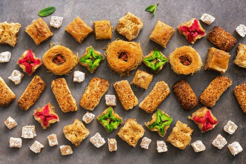 Patroon van oostelijke zoete baklava op een bruine rustieke achtergrond Arabisch dessert Lucht mening stock afbeelding