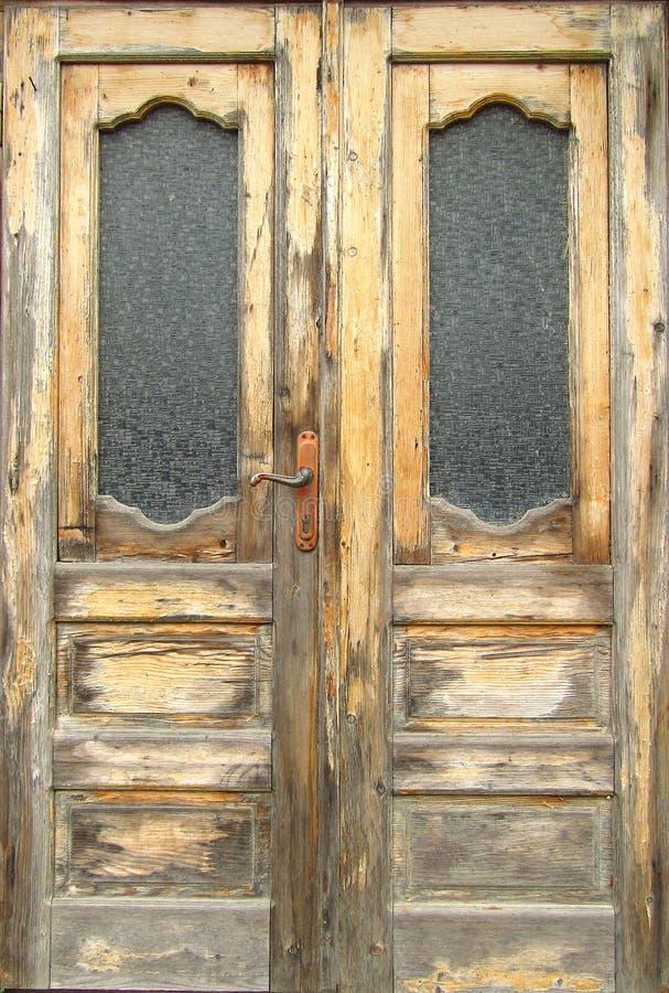 Patroon van oude houten dubbele die deur met de buitenkant van glasruiten aan het weer wordt blootgesteld Close-up stock foto's
