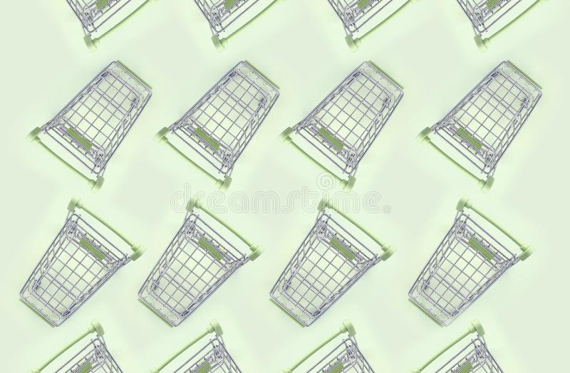 Patroon van vele kleine boodschappenwagentjes op een kalkachtergrond stock afbeelding