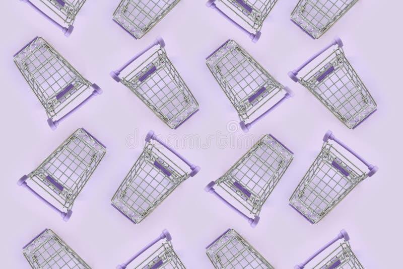 Patroon van vele kleine boodschappenwagentjes op een violette achtergrond De Minimalismvlakte legt hoogste mening stock afbeelding