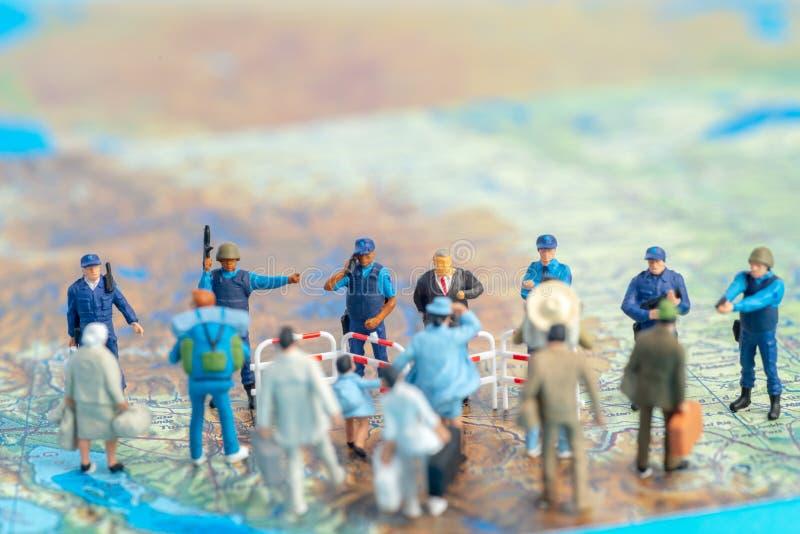 Patrulhas fronteiriças diminutas dos E.U. do conceito dos povos do brinquedo contra um grupo de emigrante foto de stock