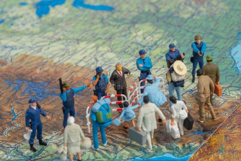 Patrulhas fronteiriças diminutas dos E.U. do conceito dos povos do brinquedo contra um grupo de emigrante imagens de stock