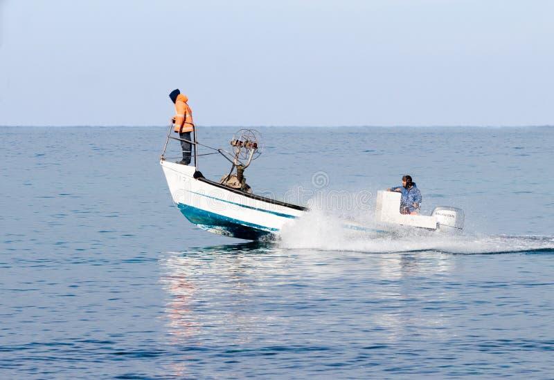 Patrulla de los pescadores en el barco y pescados el buscar foto de archivo