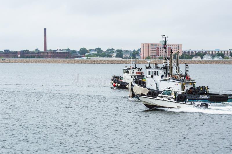 Patrullfartyg och två bogserbåtar royaltyfria foton