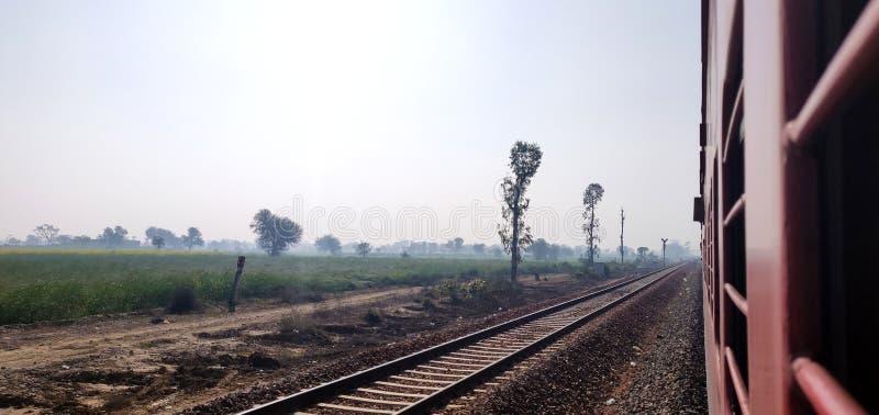 Patrzeć z okno pociąg ekspresowy Indiańskie koleje z widokiem zielonych rolnych ziemi obraz stock
