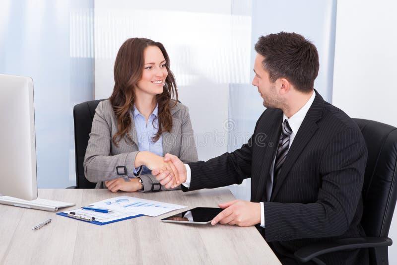 Patrzeć biznesmena wręcza przy biurowym biurkiem podczas gdy potrząsalny zdjęcie royalty free