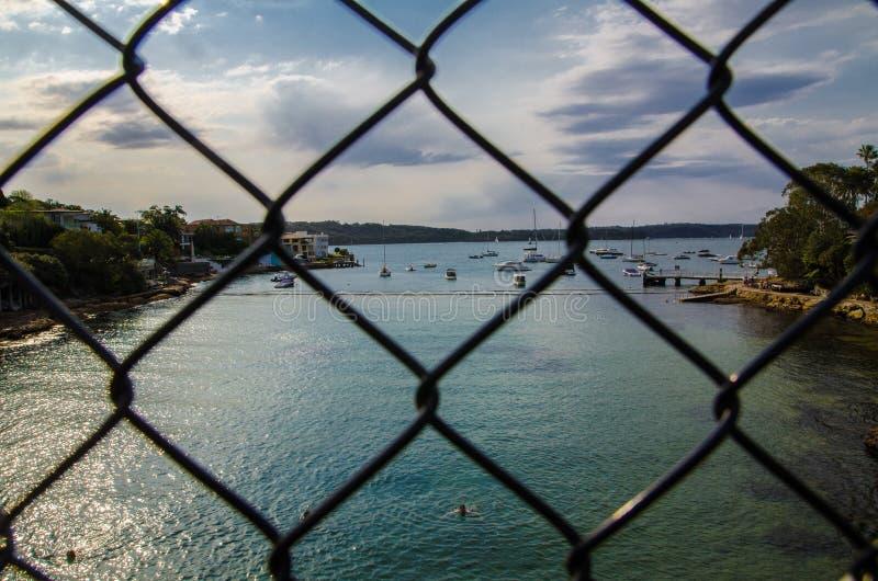 Patrzeć przez ogrodzenia pietruszki zatoki most i widzii pięknego widok zatoka z ładną morze powierzchnią, łodzią i fotografia royalty free