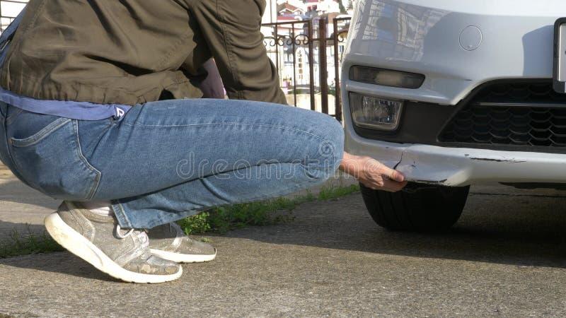 Patrzeć uszkadzającego pojazd Kobieta sprawdza samochód szkodę po wypadku zdjęcie royalty free