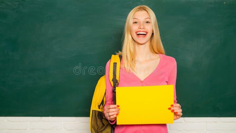 Patrze? dla wolontariusz?w formalna edukacja Ono ulepsza? przez edukaci Szczęśliwy dziewczyny mienia zawiadomienie podczas gdy fotografia royalty free