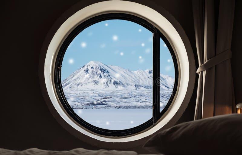 Patrzejący przez okno w zimie, śniegu krajobrazie, marznącym jeziorze z górą i śnieżnym spadku w zima ranku, fotografia stock