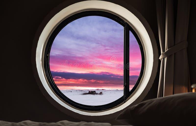 Patrzejący przez okno w zimie, przy wieczór zmierzchem obrazy royalty free