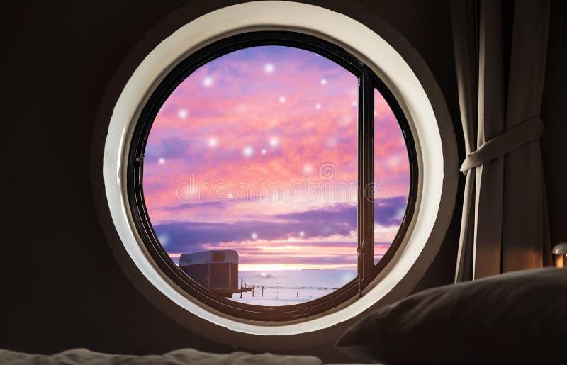 Patrzejący przez okno w zimie, przy wieczór zmierzchem z śnieżnym spadkiem w zimie zdjęcia royalty free