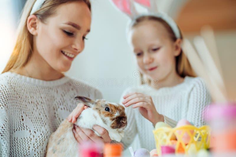 Patrzeje czym śliczny królik! Mała córka z jej macierzystym uderzeniem domu dekoracyjny królik obrazy stock