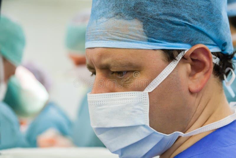 Patrzeje męskiego chirurga funkcjonujący pokój obraz stock