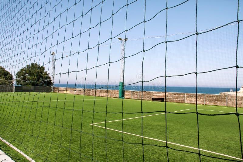 Patrzeje przez sieci opróżniać boisko piłkarskie w stadium piłkarski Boisko do piłki nożnej z zieloną trawą w futbolowym sporta s obrazy stock