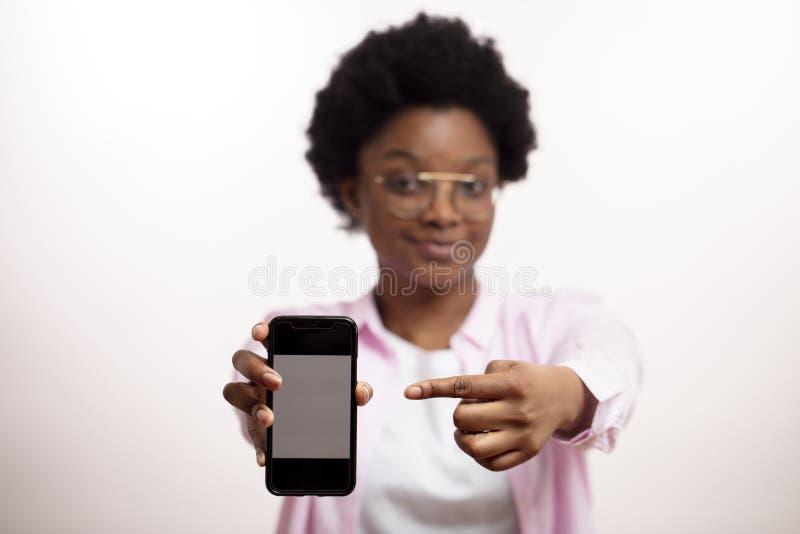 Patrzeje tutaj zadawala przyjemna uśmiechnięta kobieta reklamuje modnego mądrze telefon zdjęcie royalty free