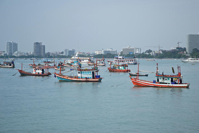 Pattaya Bay. Port fishing boats in the bay in Pattaya, Thailand, resort in the background royalty free stock image