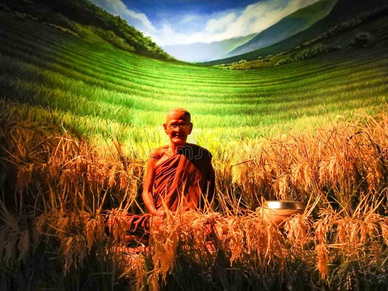 Pattaya Chonburi, Tailandia, el 27 de julio de 2017: la figura de cera del monje venerable tailandés con el árbol del arroz foto de archivo libre de regalías