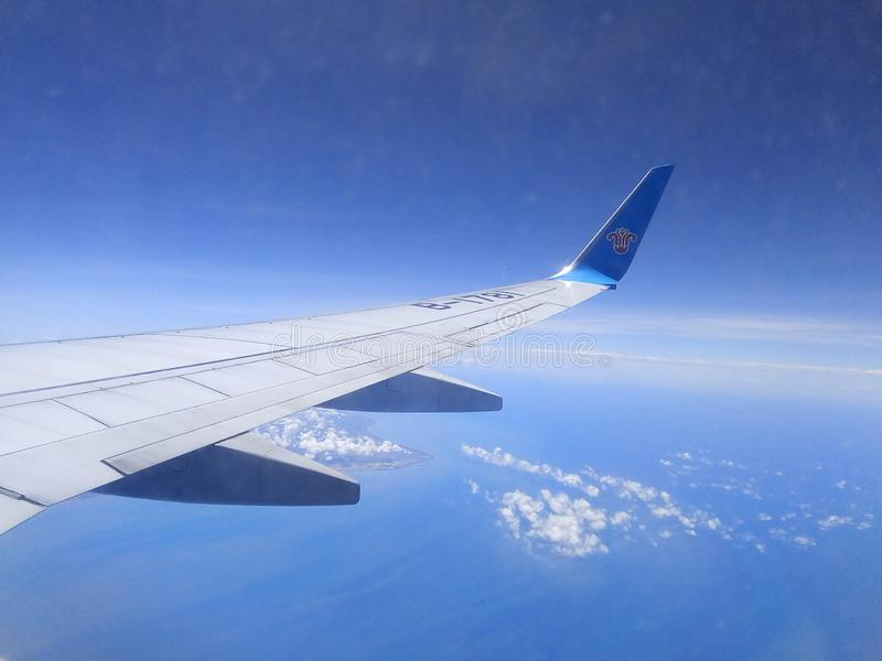 Commercial airplane flying above blue sky stock photography