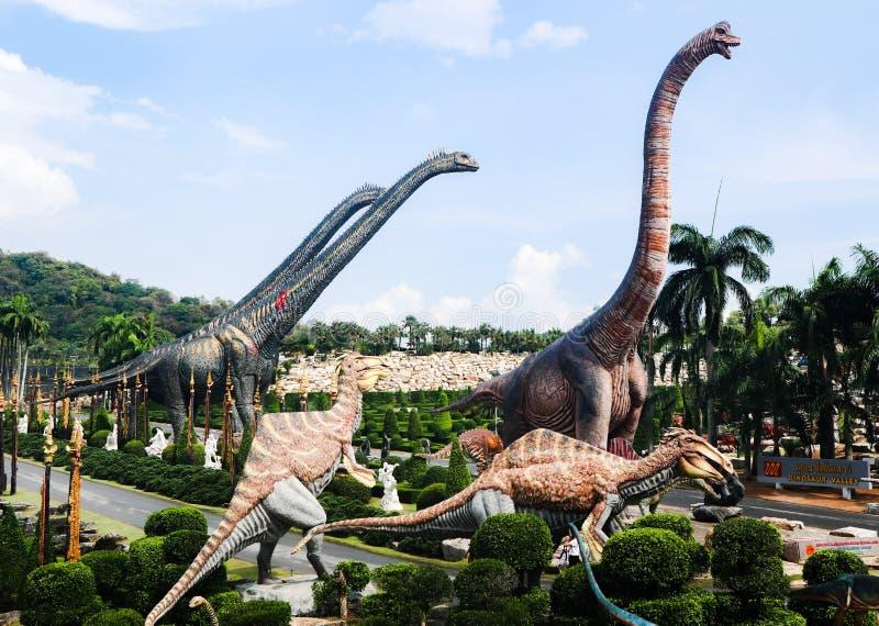 PATTAYA, TAIL?NDIA - 24 DE ABRIL DE 2019: Vale gigante do dinossauro da visita do turista no jardim de Nong Nooch imagens de stock royalty free