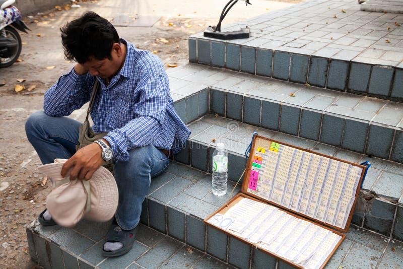Pattaya, Thaïlande - 28 mars 2016 : Séance fatiguée de vendeur de loterie image stock