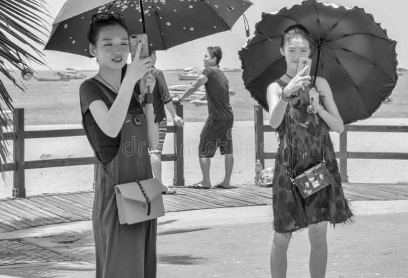 Two young and beautiful Chinese women were shooting the events on the last day of Songkran, stock photo