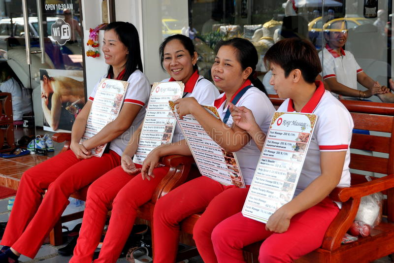 Pattaya, Thailand: Thai Mssage Women. Four Thai women sitting on a bench in front of the O Ring Massage Spa holding price signs waiting for clients in Pattaya royalty free stock photos