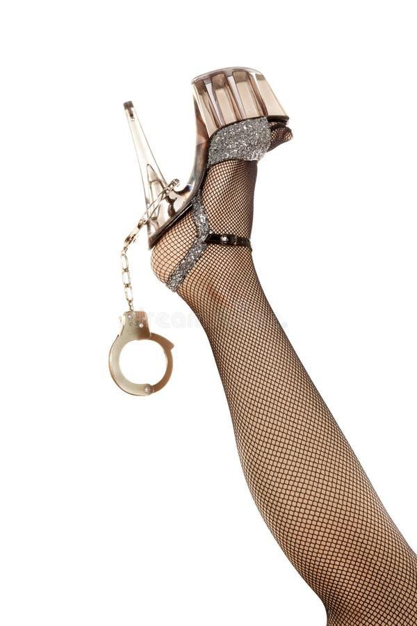 Patte de femme avec la chaussure et les menottes photographie stock libre de droits