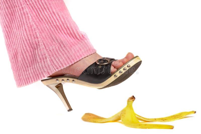 Patte femelle (pied) et peau d'une banane. Assurance-vie. image libre de droits