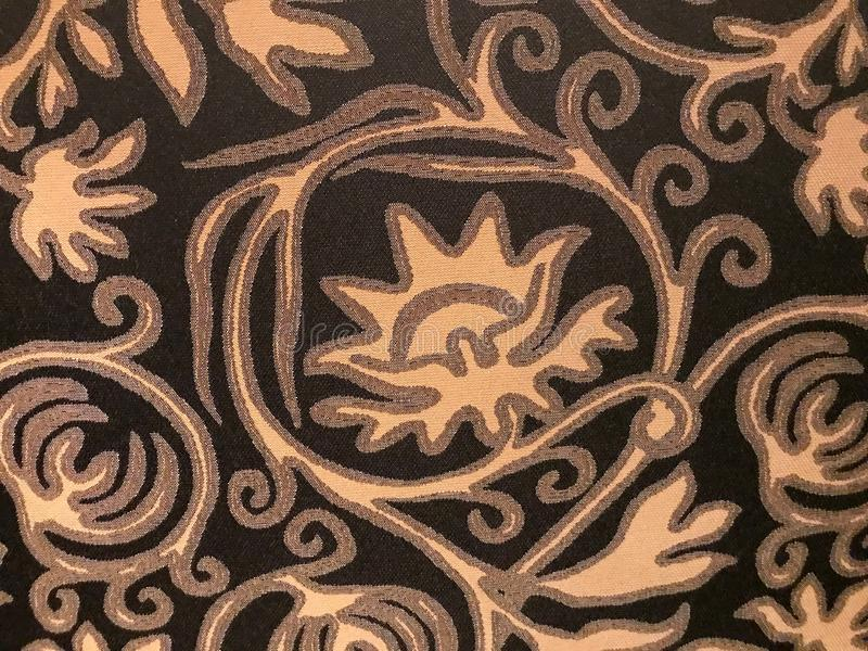 Pattern, abstract, tan, light brown, on dark background. Comes from the upholstery on a chair at the Skirvin Hotel in Oklahoma City royalty free stock image