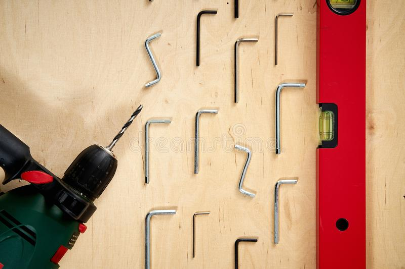 Pattern background of various allen keys with drill and level spirit on wooden work table. Pattern background of various allen keys with drill and level spirit stock photos