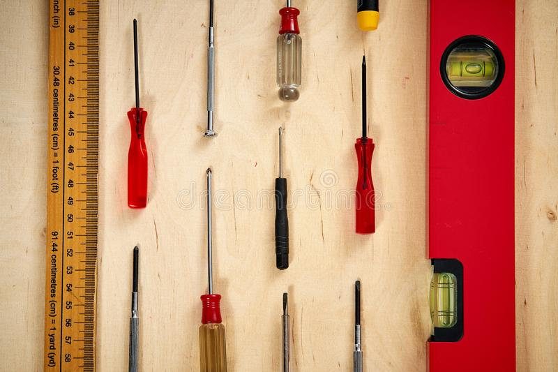 Pattern background of various screwdrivers with a spirit level and measuring tape on wooden work table. Pattern background of various screwdrivers with a spirit stock images