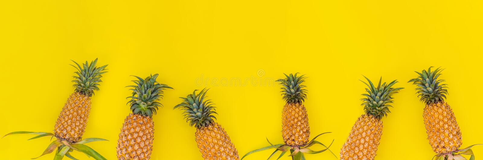 Pattern with bright pineapples on yellow background. Top View. Copy Space. Minimal style. Pop art design, creative stock photography