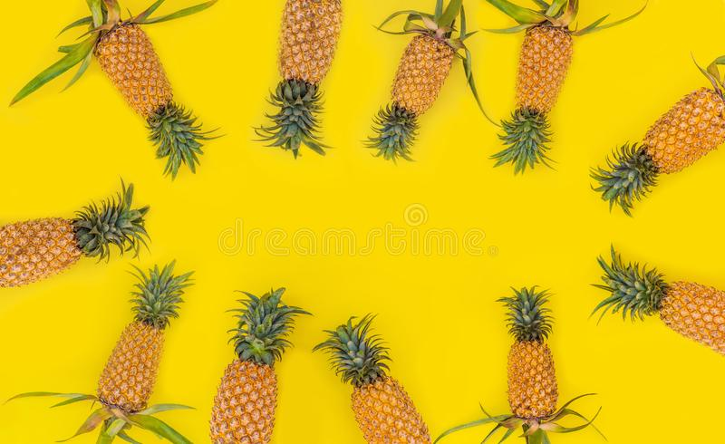 Pattern with bright pineapples on yellow background. Top View. Copy Space. Minimal style. Pop art design, creative royalty free stock photography