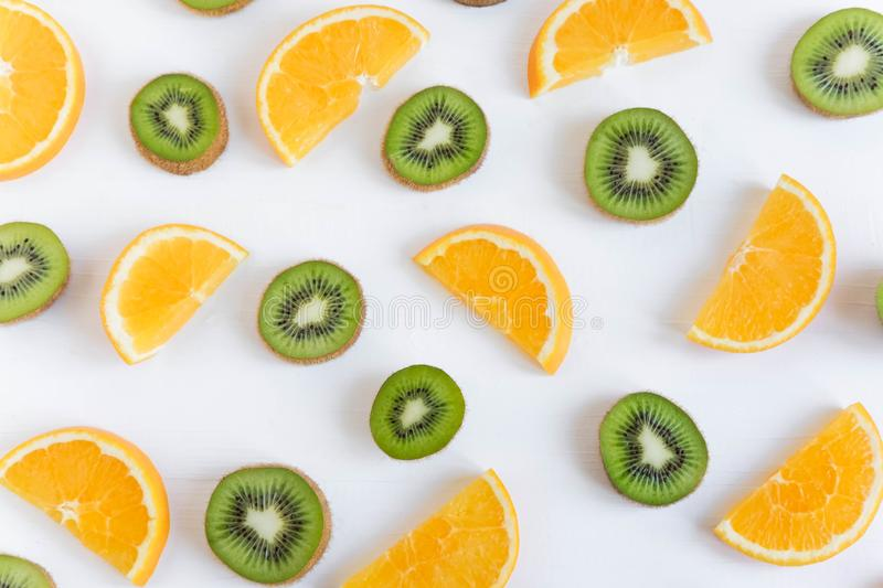 Pattern of citrus. Kiwi and orange slices on white wooden background. Healthy food. Flat lay, top view. Fresh kiwi and orange. Sliced royalty free stock photography